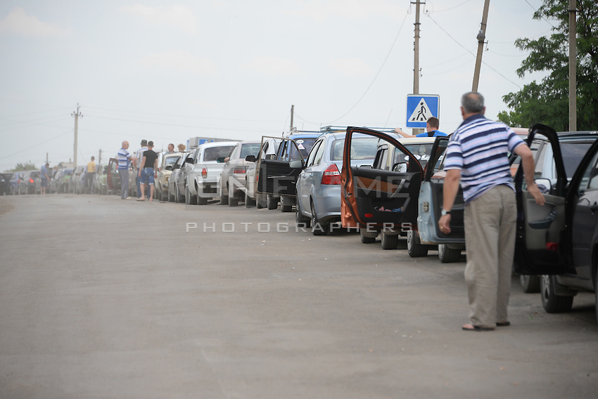 People are waiting inline at the border between Ukraine and Russia at Izvarine check point - one of border crossings controlled by Luhansk Peoples Republic. According to rebels around 5 thousand people leave Ukraine every day through Izvarine border crossing.