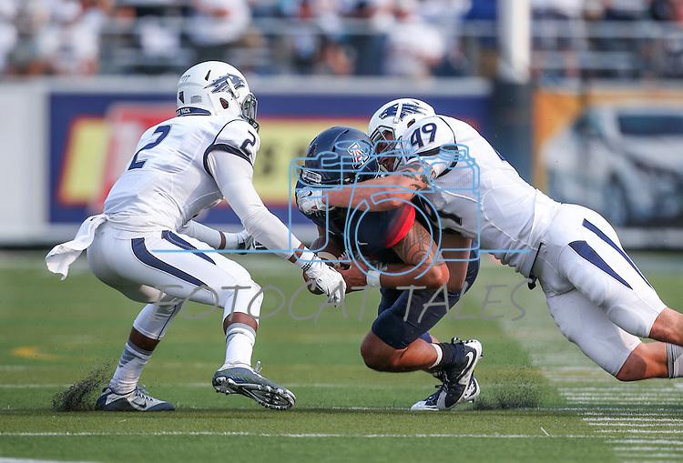 Nevada defenders Asauni Rufus (2) Jordan Dobrich (49) tackle Arizona quarterback Anu Solomon in an NCAA college football game in Reno, Nev., on Saturday, Sept. 12, 2015.(AP Photo/Cathleen Allison)