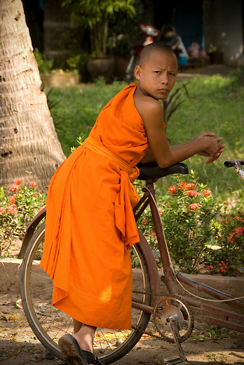 A young novice monk leans on a bicycle in Luang Prabang, Laos.  Laos is predominately a Theravada Buddhist country. Many will join the monastery for a period of time to gain merit for their families and themselves. Some stay for a short time and others will choose to devote their lives to their religion.
