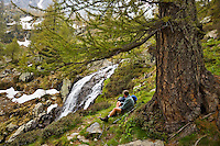 Parc National du Mercantour.  Walker rests by a mountain waterfall, tributary of the River Valmasque. Alpes-Maritimes, Provence, France.    Model released.