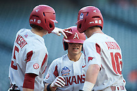 Robert Moore (1) of the Arkansas Razorbacks is congratulated at home plate by teammates Jacob Nesbit (5) and the Cole Austin (16) after hitting a two-run home run against the Oklahoma Sooners in game two of the 2020 Shriners Hospitals for Children College Classic at Minute Maid Park on February 28, 2020 in Houston, Texas. The Sooners defeated the Razorbacks 6-3. (Brian Westerholt/Four Seam Images)