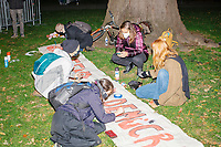 People paint protest signs as demonstrators gather in McPherson Square near the White House on the night of Election Day in Washington, D.C., on Tue., Nov. 3, 2020. Election results remained uncertain late into the night and demonstrators were peaceful.