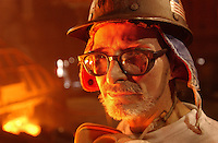 """STEEL:  BURNS HARBOR: """"Blast Furnace keeper helper"""" John Pollock  looks out over the molton iron  as the slag pours off the """"heat"""". With the American flag attached to his hard hat Pollock reflects on the intense heat of his workplace  """"if you get a cold.. you can come here and it sweats it out of you!? he says with a bit of a laugh."""" ( CHUCK ZOVKO / TMC)."""