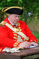 Officer of His Majesty's 53rd Regiment of Foot reviews the charges during a court martial at a Revolutionary War encampment at Freeman's Farm, site of a major British defeat in September 1777, Saratoga National Historical Park, Stillwater, New York, USA.