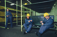 Switzerland. Canton Lucerne. Two men with yellow helmets play cards seated on bunk beds in the Sonnenberg tunnel in Lucerne during the largest civil defense exercise ever held in the country. Another man is bored and stands up alone. From 16 to 21 November 1987, almost 1200 men and women converted a motorway tunnel into perhaps the world's largest bunker structure. The civil protectors had to prove during the exercise «Ameise » ( Ants in english) that in an emergency more than 20,000 inhabitants of the city of Lucerne could survive here in the mountain for two weeks. The Sonnenberg Tunnel is a 1,550 m  long motorway tunnel, constructed between 1971 and 1976. At its completion it was also the world's largest civilian nuclear fallout shelter, designed to protect 20,000 civilians in the eventuality of war or disaster. Based on a federal law from 1963, Switzerland aims to provide nuclear fallout shelters for the entire population of the country. The construction of a new tunnel near an urban centre was seen as an opportunity to provide shelter space for a large number of people at the same time. The giant bunker was built between 1970 and 1976 at a cost of 40 million Swiss francs. The shelter consisted of the two motorway tunnels (one per direction of travel), each capable of holding 10,000 people in 64 person subdivisions. A seven story cavern between the tunnels contained shelter infrastructure including a command post, an emergency hospital, a radio studio, a telephone centre, prison cells and ventilation machines. The shelter was designed to withstand the blast from a 1 megaton nuclear explosion 1 kilometer away. The blast doors at the tunnel portals are 1.5 meters thick and weigh 350 tons. The logistical problems of maintaining a population of 20,000 in close confines were not thoroughly explored, and testing the installation was difficult because it required closing the motorway and rerouting the usual traffic. The only large-scale test, a five-day exercise in
