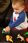 toddler boy 18 months old playing with toy truck pushing it