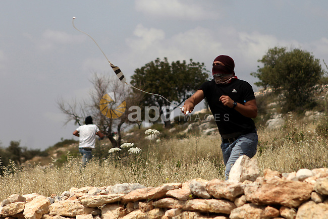A masked Palestinian protester uses a slingshot to hurl stones at Israeli security forces during clashes following a demonstration marking Palestinian Prisoners' Day, in the West Bank village of Bilin, near Ramallah on April 17, 2015. Palestinian human rights groups say 6,000 Palestinian prisoners remain in Israeli prisons and detention camps. Photo by Shadi Hatem