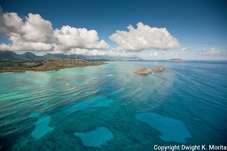 The clouds in the sky mimic the patches of sand in the reef, in the beautiful waters surrounding the Mokulua Islands in Lanikai, Kailua, Hawaii
