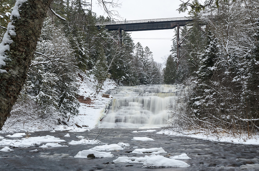 A wintertime view of Agate Falls from the river with the historic railroad bridge crossing above. Trout Creek, MI