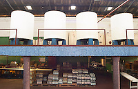 Two levels in the winery: on top concrete fermentation tanks painted white and blue and below the bottling line with pallets of bottles ready to ship Bodega Plaza Vidiella Winery, Las Brujas, Canelones, Uruguay, South America