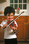 smiling young boy playing violin in kitchen