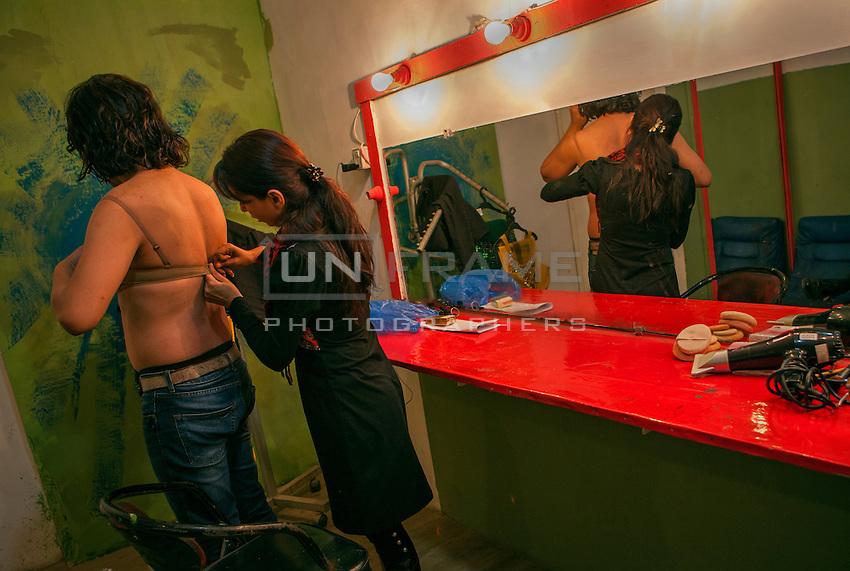An assistant helps Ali Saleem to wear his bra.