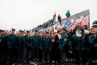 People climbing on the Berlin Wall a few days after its opening on November 9, 1989. Thousands climbed on the Wall as news spread rapidly that the East German Government would now start granting exit visas to anyone who wanted to go to the West. The announcement was misinterpreted as meaning the border was now open and East German border guards were unable to stop the rush of people to the Wall. Within hours people were smashing sections of the Wall with their own hand tools and these first cracks led to the complete opening of the border within days.