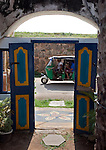 An autorickshaw passes by the doorway of the Pilgrim cafe in the city of Galle in southern Sri Lanka which  was devastated by the massive Boxing Day Tsunami caused by the 2004 Indian Ocean earthquake that occurred a thousand miles away, off the coast of Indonesia. Thousands were killed in the city alone..Galle is the best example of a fortified city built by Europeans in south and southeast Asia, showing the interaction between European architectural styles and south Asian traditions. The Galle fort is a world heritage site and the largest remaining fortress in Asia built by European occupiers. .Galle is the main town in the most southerly part of the island, with a population of around 100,000, and is connected by rail to Colombo and Matara. It is home to a cricket ground, the Galle International Stadium, rebuilt after the 2004 tsunami. Test matches resumed there on December 18, 2007.