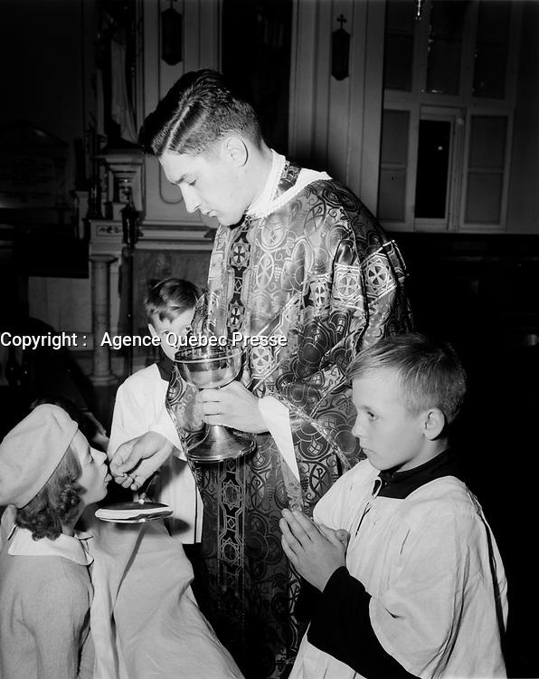 Messe  catholique <br /> des peres blanc, a Cap Rouge<br /> ,Septembre 1952 - le pretre donne la communion aide par les jeunes servants de messeé<br /> <br /> PHOTO :  Agence Quebec Presse
