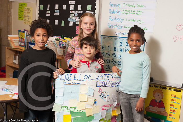 Education Elementary school Grade 2 students working on small group projects, group posing with their finished project on bodies of water