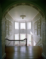 Looking back down the staircase to two tiers of windows surrounded by rococo plasterwork panels attributed to Robert West