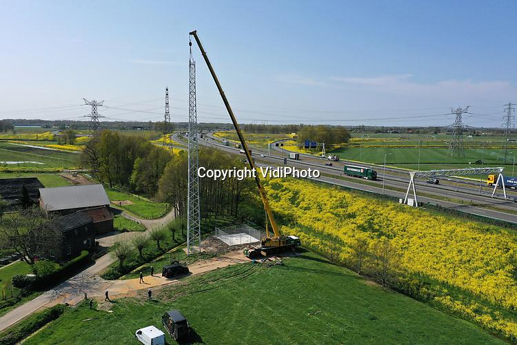 Foto: VidiPhoto<br /> <br /> VALBURG – Langs de A50 bij knooppunt Valburg wordt vrijdagmiddag door installatiebedrijf WL Winet uit Eindhoven een brandvrije metalen zendmast geplaatst voor draadloze telecommunicatie. De mast is ook geschikt voor het snelle 5G-netwerk straks en wordt daarom extra beveiligd. Inwoners van Valburg zijn niet blij met de plek van de mast, die aan de rand van het dorp komt te staan. Ze vrezen extra (stralings)overlast, terwijl het dorp al steeds meer wordt ingekapseld door infrastructurele werken als A50, A15, Betuwelijn, hoogspanningsmasten en een railterminal voor containeroverslag. Het netwerk bij Valburg komt pas naar verwachting over een half jaar in bedrijf omdat alle kabels en leidingen naar de mast nog moeten worden aangelegd.