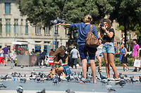 Tourists with pigeons at Catalonia Square, Barcelona, Spain