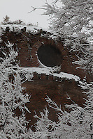 Rome, villa Gordiani: An ancient building with a round opening in villa Gordiani, on the Prenestina road. The ancient beauty is enhanced by the peculiar a snow-clad frame, since the view is taken after a snowing night, and the building is surrounded by bare tree branches, that are covered by snow, too (February 2012).