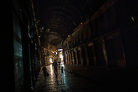 A family walk through the empty streets of the souk in old town Damascus, Syria. Shops which would once have been still busy at this time now close their doors early as most people no longer venture out after dark.