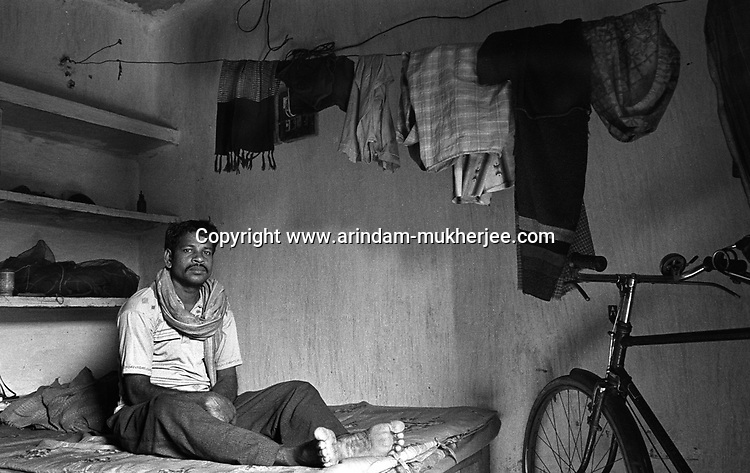 A loader of a mine sits on his bed in his one roomed quarter. He lives alone there. Most of the miners leave their families back in their villages. Generally these labourers are from the neighbouring states of Bihar and Orissa. North Searsole Coliery in Ranigunj, West Bengal, India. Ranigunj, West Bengal, India. Arindam Mukherjee