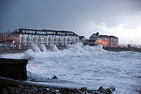 Pictured: Huge waves crashing against the promenade wall in Porthcawl, south Wales. Friday 03 January 2014<br /> Re: Flood warnings have been issued  by the Environment Agency due to strong winds and high tides for part of the UK.