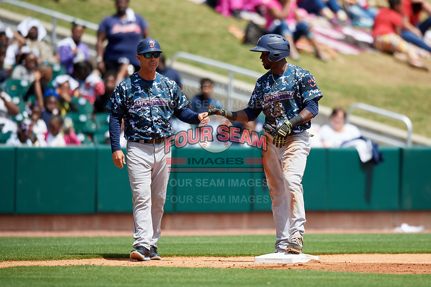 Jacksonville Jumbo Shrimp manager Randy Ready (5) first bumps left fielder Jeremias Pineda (20) after he slid into third base safely during a game against the Birmingham Barons on April 24, 2017 at Regions Field in Birmingham, Alabama.  Jacksonville defeated Birmingham 4-1.  (Mike Janes/Four Seam Images)
