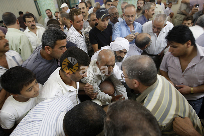Palestinian men touch a glass tube during a special prayer following Laylat al Qadr at a mosque in the West Bank city of Nablus Sept 6, 2010. Some local Muslims believe the tube contains a hair from the beard of the Prophet Mohammad . Photo by Wagdi Eshtayah