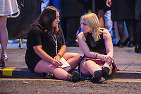 Saturday  17 December 2016<br /> Pictured: Girls sit on the road and chat <br /> Re: Swansea City Centre and the notorious Wind street, often nicknamed 'Wine Street' is packed full of Christmas jumpers and glitzy dresses as thousands head to office dos across the UK in the biggest party night of the year.