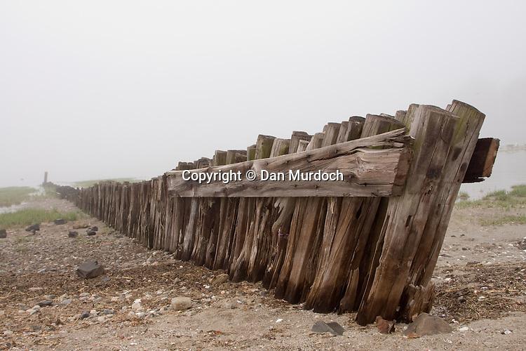 wood breakwater on misty morning