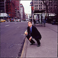 Man in suit kneeling on the sidewalk holding a banana and posturing as an ape<br />