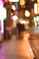 AVAILABLE FOR COMMERCIAL OR EDITORIAL LICENSING FROM GETTY IMAGES.  Please go to www.gettyimages.com and search for image # 163063388.<br /> <br /> Defocused View of a Couple Walking on an Illuminated Street at Night in Chinatown, Lower Manhattan, New York City, New York State, USA