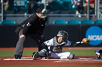 Coastal Carolina Chanticleers catcher BT Riopelle (25) frames a pitch as home plate umpire Craig Mirr looks on during the game against the Illinois Fighting Illini at Springs Brooks Stadium on February 22, 2020 in Conway, South Carolina. The Fighting Illini defeated the Chanticleers 5-2. (Brian Westerholt/Four Seam Images)