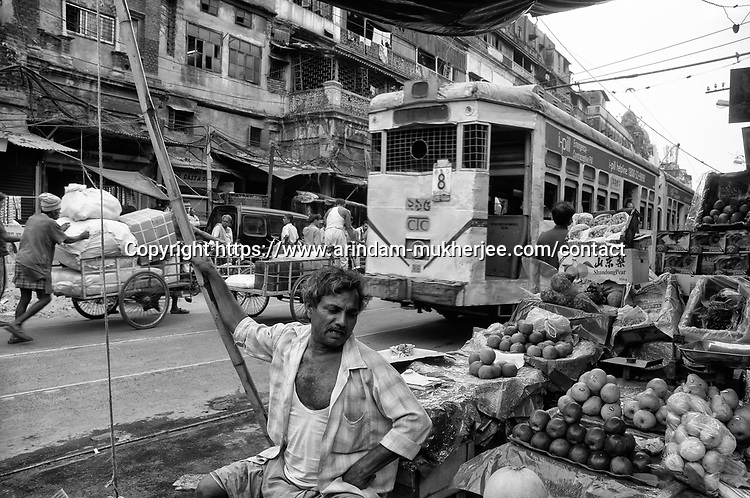 A street fruit seller at his shop while a tram passes by in Kolkata, India.
