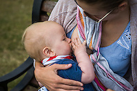 """A young mother breastfeeding her baby while sitting on a park bench.<br /> <br /> Image from the breastfeeding collection of the """"We Do It In Public"""" documentary photography picture library project: <br />  www.breastfeedinginpublic.co.uk<br /> <br /> <br /> Dorset, England, UK<br /> 2015<br /> <br /> © Paul Carter / wdiip.co.uk"""