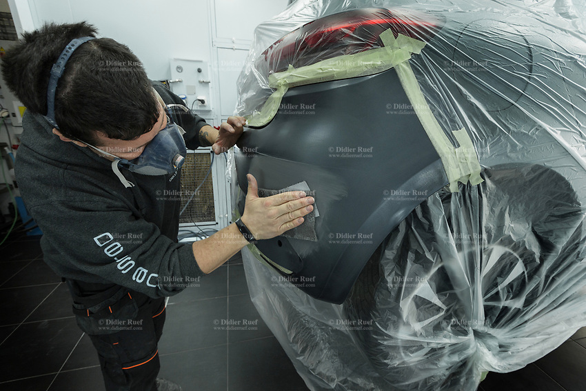 """Switzerland. Canton Geneva. Plan-les-Ouates. Renault Retail Group, RRG Suisse. """"Spot-repair"""" by Dells Angels. Renault Clio car inside a paint booth in auto body repair garage. After filling bumpy part, the mechanic worker is hand grinding automobile car body in garage workshop.  4.03.2020 © 2020 Didier Ruef"""