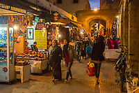 Essaouira, Morocco.  Evening Street Scene, Shops Selling Cell Phones and Thuya Wood Souvenirs.