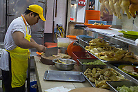 Kitchen Worker Cutting Chicken in Lou Wong Restaurant, Famous for Chicken, Rice, and Bean Sprouts (Tauge Ayam), an Ipoh Specialty.  Ipoh, Malaysia.