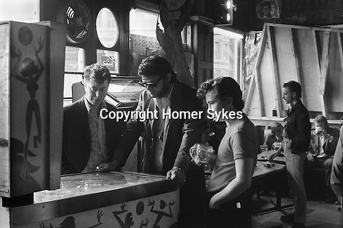 Moorgate, London. 1975<br /> Playing a pinball machine at The Black Raven in Bishopgate Street,<br /> Sunglasses Ron Staples, styled himself the King of the Teds the Edwardian Teddy Boy<br /> <br /> Sunglasses Ron Staples, died in 1999?