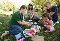 Marie Parks (from left), children's librarian at the West Fork Public Library, shows how to dye wool yarn Tuesday, Sept. 7, 2021, as Bethany White, her son, Axyl White, 2, Sophie Jett, 3, and her mother, Trish Jett, all of Winslow, listen during story time in a clearing outside the library. The day's story and activity had to do with sheep, wool and how wool is processed. Library staff took a break from hosting story time during August, but is back to hosting visitors at 10 a.m. on Tuesdays. Visit nwaonline.com/210908Daily/ for today's photo gallery.<br /> (NWA Democrat-Gazette/Andy Shupe)