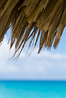 Edge of a sun umbrella straw with blue waters in the background, Cayo Santa-Maria, Cuba.