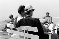 Greece. Cyclades. Tourists on holiday travel on a ferry in between two islands. Couples rest and sit on wooden benches. A ferry (or ferryboat) is a boat or ship (a merchant vessel) used to carry (or ferry) primarily passengers, and sometimes vehicles and cargo as well, across a body of water. Most ferries operate on regular frequent return services. 25.06.92 © 1992 Didier Ruef