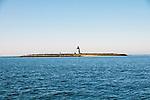 Approaching Bird Island by boat, wide shot from water.