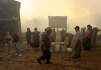 Porqueira´s neighbors are seen around with a bucket near fires in Porqueira, August 14, 2010, near A Coruña. Pedro ARMESTRE