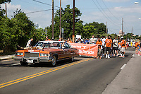 """AUSTIN, TEXAS - A vintage cadillac painted in """"burnt orange"""" with longhorns mounted on the hood drives along the University of Texas Athletics Department at the 2016 Central Texas Juneteenth Celebration Parade on on Sat. June 18, 2016. <br /> <br /> Use of this image in advertising or for promotional purposes is prohibited.<br /> <br /> Editorial Credit: Photo by Dan Herron / Herron Stock"""