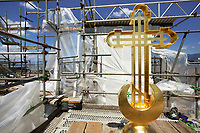 """Switzerland. Geneva.The Russian Church (full name: Cathédrale de l'Exaltation de la Sainte Croix) is designed in a Byzantine Moscovite style. The church is a lovely 19th-century Russian Orthodox church topped with golden onion domes. The building, roof and bulbs undergo a complete revival restoration. The cross has already been covered by a thin coating of gold. The term gilding covers a number of decorative techniques for applying fine gold leaf to solid surfaces such as onion domes and crosses. A gilded object is also described as """"gilt"""". The Russian church serves today not only the Russian community but also Bulgarians, Serbs, Coptic Christians and other Orthodox worshippers who do not have their own church in Geneva. In the background, the Jet d'Eau (Water-Jet) which is a large fountain on lake Geneva and is one of the city's most famous landmarks.<br /> An onion dome is a dome whose shape resembles an onion. Such domes are often larger in diameter than the drum upon which they sit, and their height usually exceeds their width. These bulbous structures taper smoothly to a point. 28.06.2016 © 2016 Didier Ruef"""