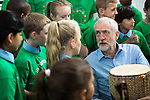 © Joel Goodman - 07973 332324 . 27/09/2016 . Liverpool , UK . Labour Party leader JEREMY CORBYN with a bongo drum during a visit to Faith Primary School in Liverpool , where he listens to and then joins in with the school orchestra . Photo credit : Joel Goodman