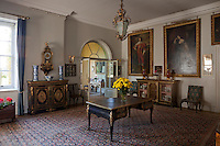 An ornate gilt lantern hangs above an antique desk in  a reception room. 17th century swagger portraits hang on the wall behind