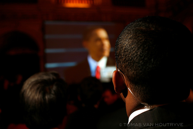 A member of the security detail of the U.S. ambassador to France watches the inauguration speech of Barack Obama on a screen with live coverage of the U.S. presidential inauguration inside the Hotel de Ville (City Hall) of Paris, France.